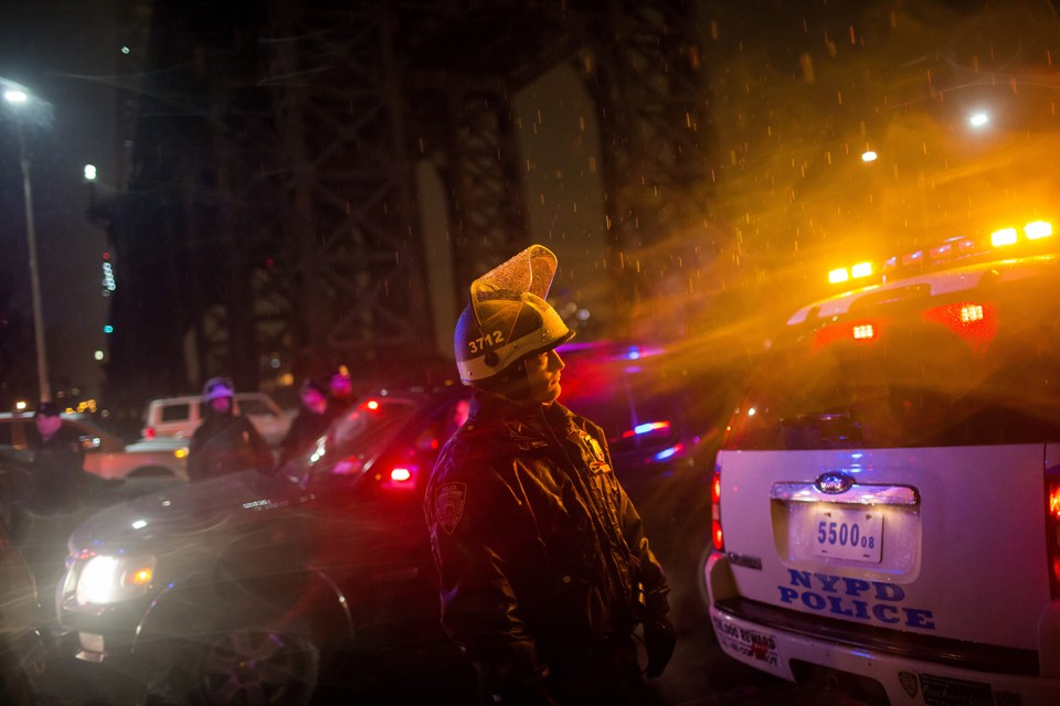 A police officer keeps watch along FDR Drive, as thousands of demonstrators took to the streets demanding justice for the death of Eric Garner, in Manhattan